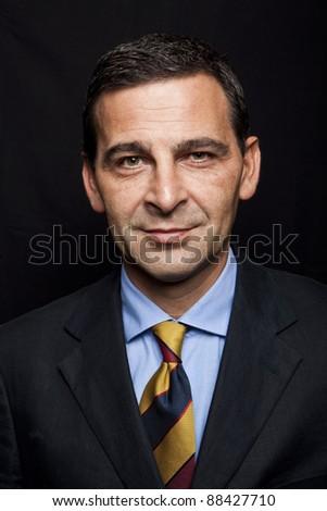 Portrait of confident businessman over black background - stock photo