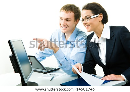 Portrait of confident businessman pointing at computer talking about work with woman near by