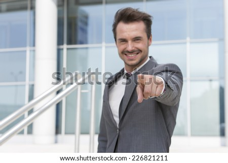 Portrait of confident businessman pointing at you outside office building - stock photo