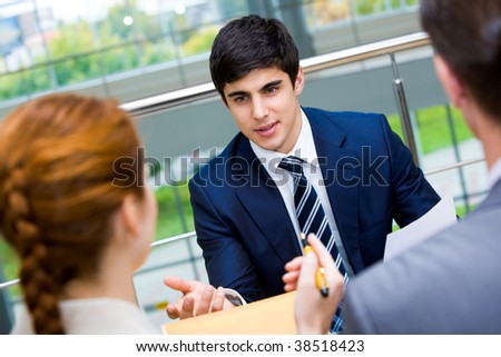 Portrait of confident businessman sharing his ideas with associates at meeting - stock photo