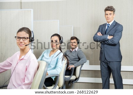 Portrait of confident businessman standing arms crossed by team in call center - stock photo