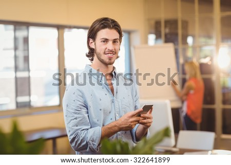 Portrait of confident businessman texting on phone with female colleagues looking at whiteboard in creative office - stock photo