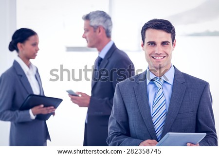 Portrait of confident businessman using a tablet with colleagues behind in office - stock photo