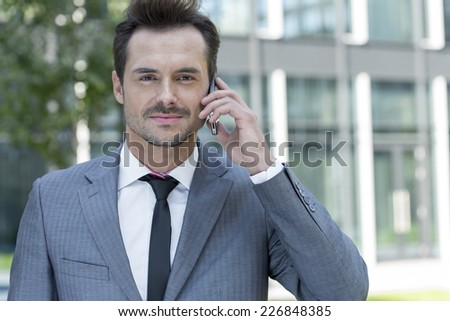 Portrait of confident businessman using cell phone outside office - stock photo