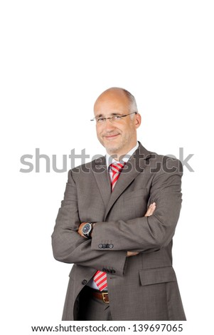 Portrait of confident businessman with arms crossed standing over white background - stock photo