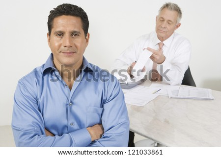 Portrait of confident businessman with colleague in background