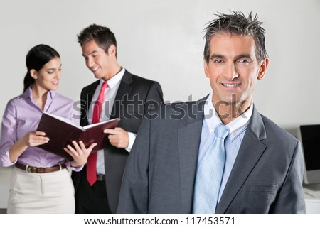 Portrait of confident businessman with colleagues discussing in background - stock photo