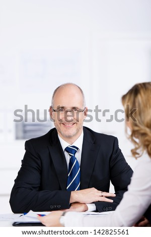 Portrait of confident businessman with coworker in foreground at office desk