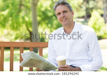 Portrait of confident businessman with disposable cup and newspaper in the park - stock photo