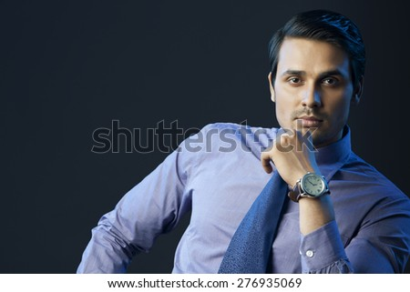Portrait of confident businessman with hand on chin over black background