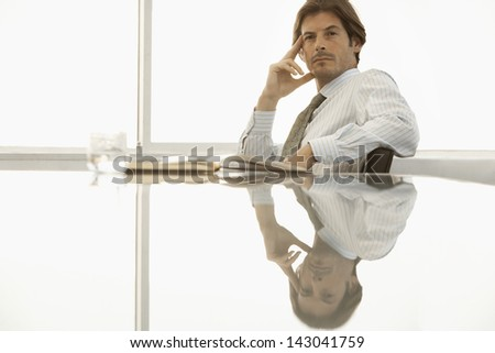 Portrait of confident businessman with hand on face sitting at conference table - stock photo