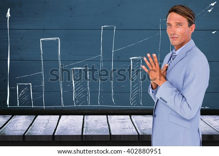Portrait of confident businessman with hands clasped against a red wall - stock photo