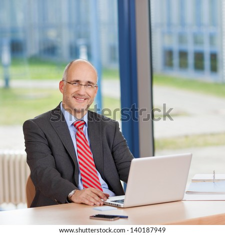 Portrait of confident businessman with laptop sitting at office desk - stock photo