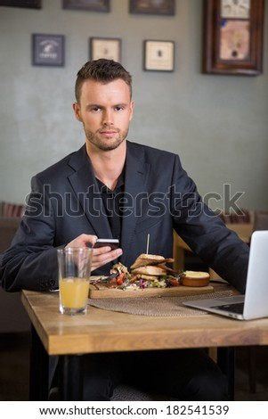 Portrait of confident businessman with mobilephone and laptop having sandwich in coffeeshop - stock photo