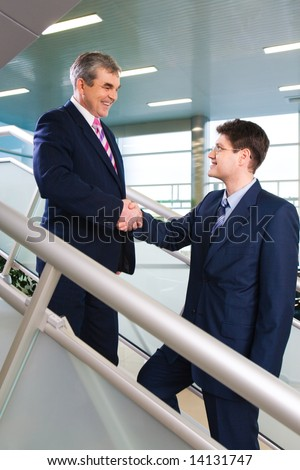 Portrait of confident businessmen handshaking in the modern office building during meeting - stock photo