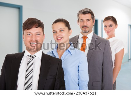 Portrait of confident businesspeople smiling together in office