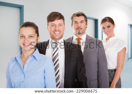 Portrait of confident businesspeople standing together in office - stock photo
