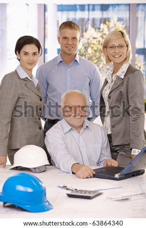 Portrait of confident businessteam standing with senior executive sitting at desk in middle, smiling at camera.? - stock photo