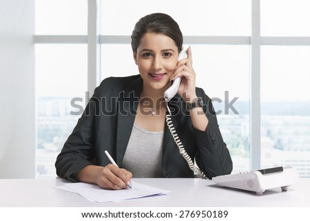 Portrait of confident businesswoman answering telephone at office desk