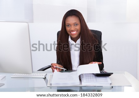 Portrait of confident businesswoman calculating tax at desk in office - stock photo