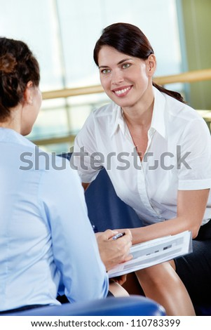 Portrait of confident businesswoman consulting her colleague in the office