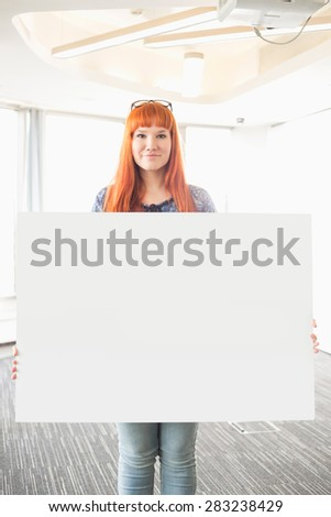 Portrait of confident businesswoman holding blank placard in creative office - stock photo