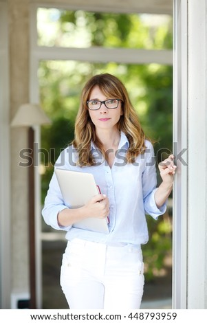 Portrait of confident businesswoman holding hand her laptop while standing at home after finishing job.  - stock photo