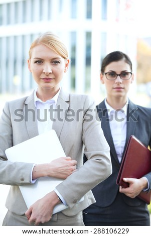 Portrait of confident businesswoman holding laptop with colleague in background - stock photo