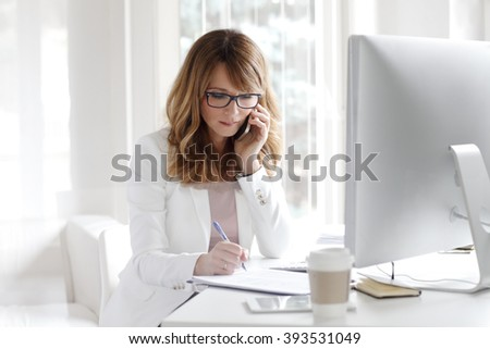 Portrait of confident businesswoman making call and doing paperwork at her workplace in front of computer.
