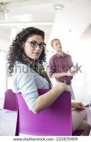 Portrait of confident businesswoman sitting on chair with colleague standing in background at creative office - stock photo
