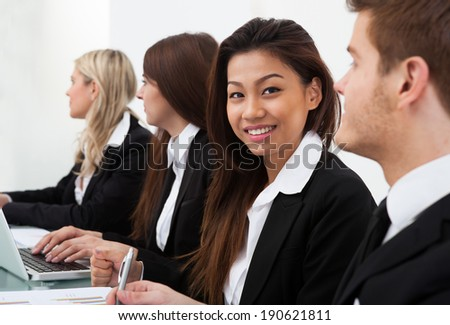 Portrait of confident businesswoman sitting with colleagues in meeting at office - stock photo