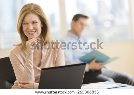 Portrait of confident businesswoman smiling with colleague sitting in background at office - stock photo