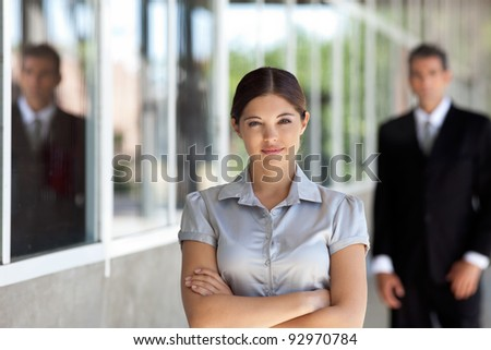 Portrait of confident businesswoman standing arms crossed with man standing in background