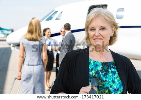 Portrait of confident businesswoman with airhostess greeting business people near private jet - stock photo