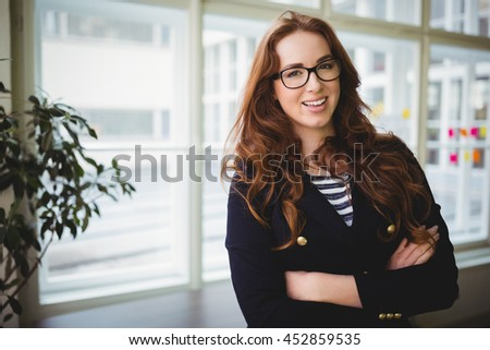 Portrait of confident businesswoman with arms crossed in creative office - stock photo
