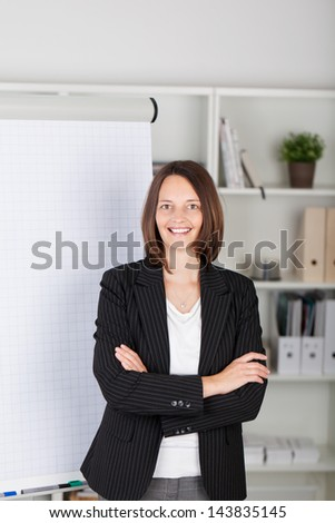 Portrait of confident businesswoman with arms crossed standing against flipchart in office - stock photo