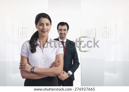 Portrait of confident businesswoman with colleague in background at office - stock photo