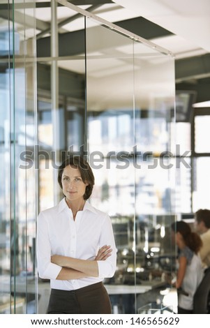 Portrait of confident businesswoman with colleagues working in background - stock photo
