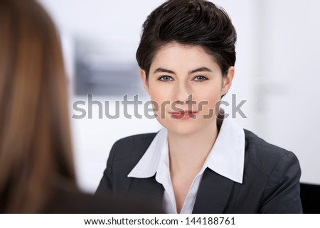 Portrait of confident businesswoman with coworker in foreground in office - stock photo