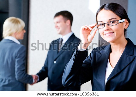 Portrait of confident businesswoman with glasses standing in the office on the background of people shaking hands