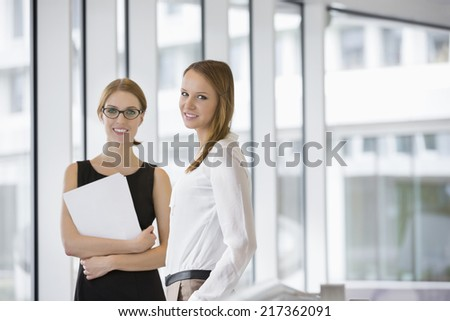 Portrait of confident businesswomen with documents in office