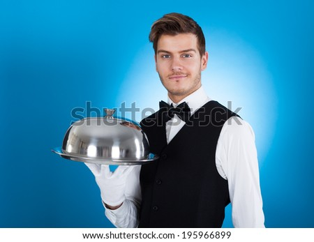 Portrait of confident butler carrying tray over blue background - stock photo