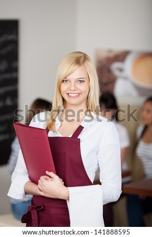 Portrait of confident cafe waitresses holding menu in cafe - stock photo