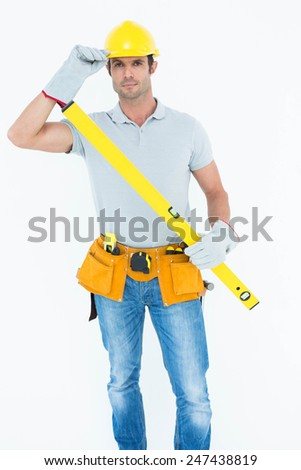 Portrait of confident carpenter holding spirit level while wearing hard hat over white background - stock photo