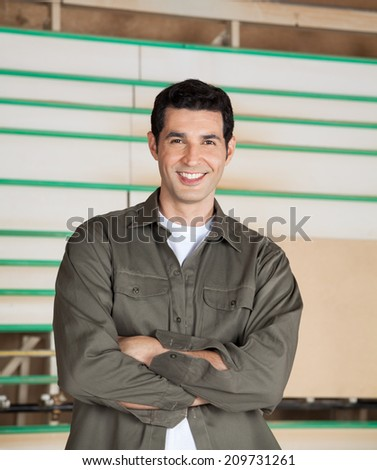 Portrait of confident carpenter standing arms crossed in workshop