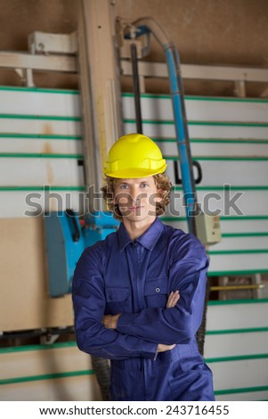 Portrait of confident carpenter with arms crossed standing against vertical saw machine in workshop