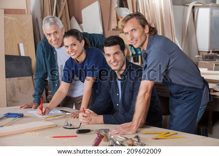 Portrait of confident carpenters working together at table in workshop - stock photo