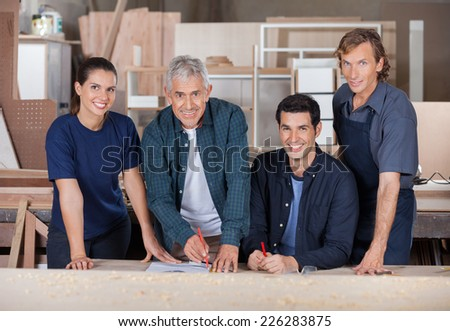 Portrait of confident carpenters working together in workshop - stock photo