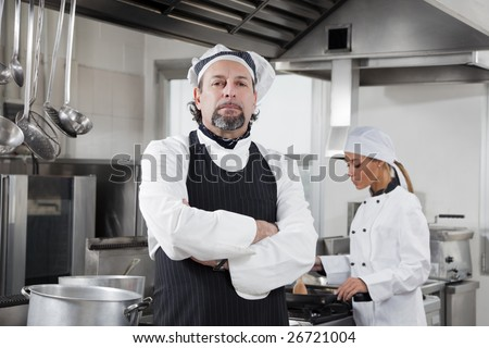 portrait of confident chef looking at camera in kitchen - stock photo