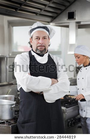 portrait of confident chef looking at camera in kitchen